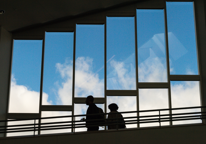 In a campus building, two students walk past windows that show a blue sky outside.