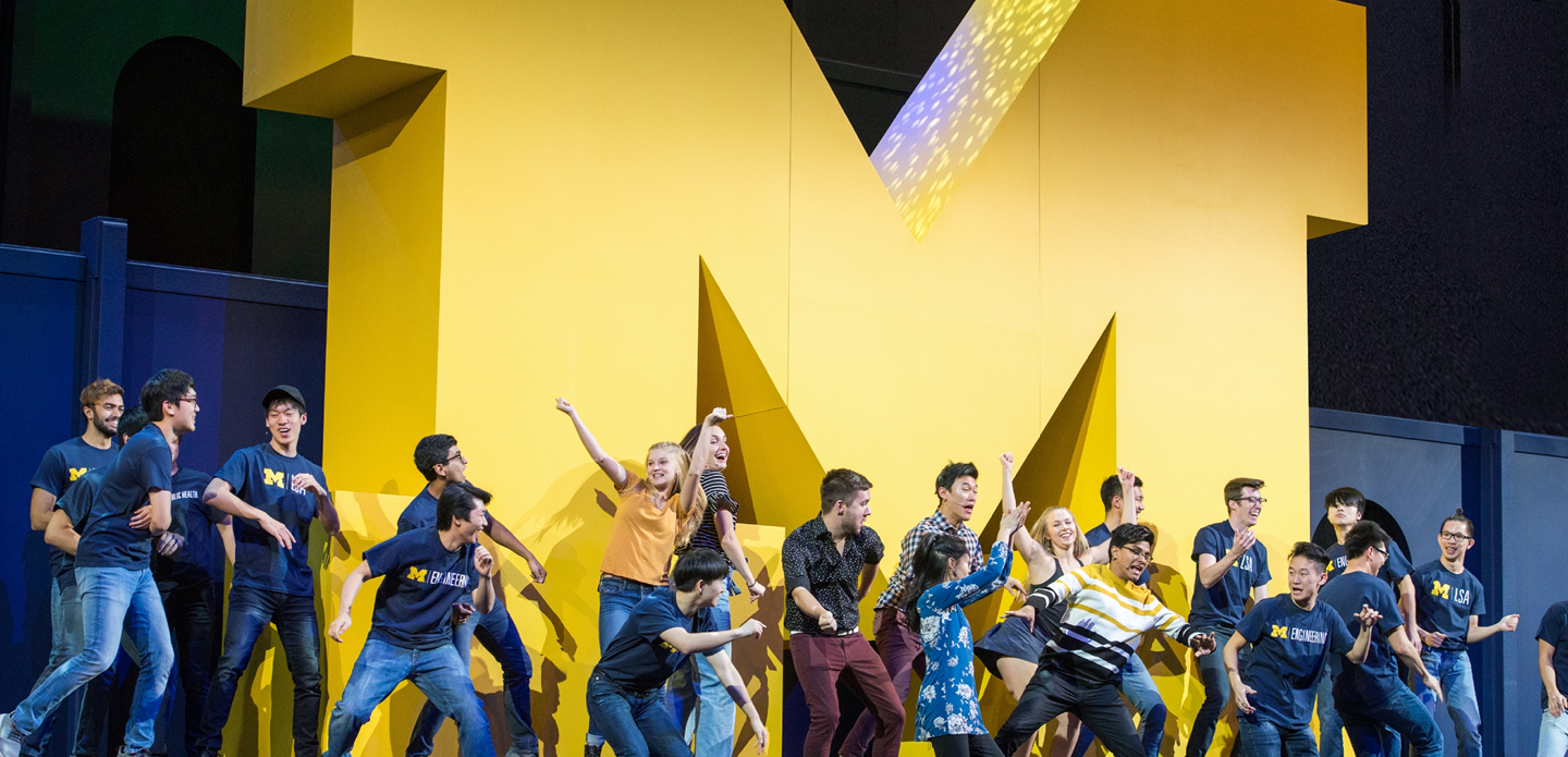 U-M students dance onstage in front of a big yellow Block M.