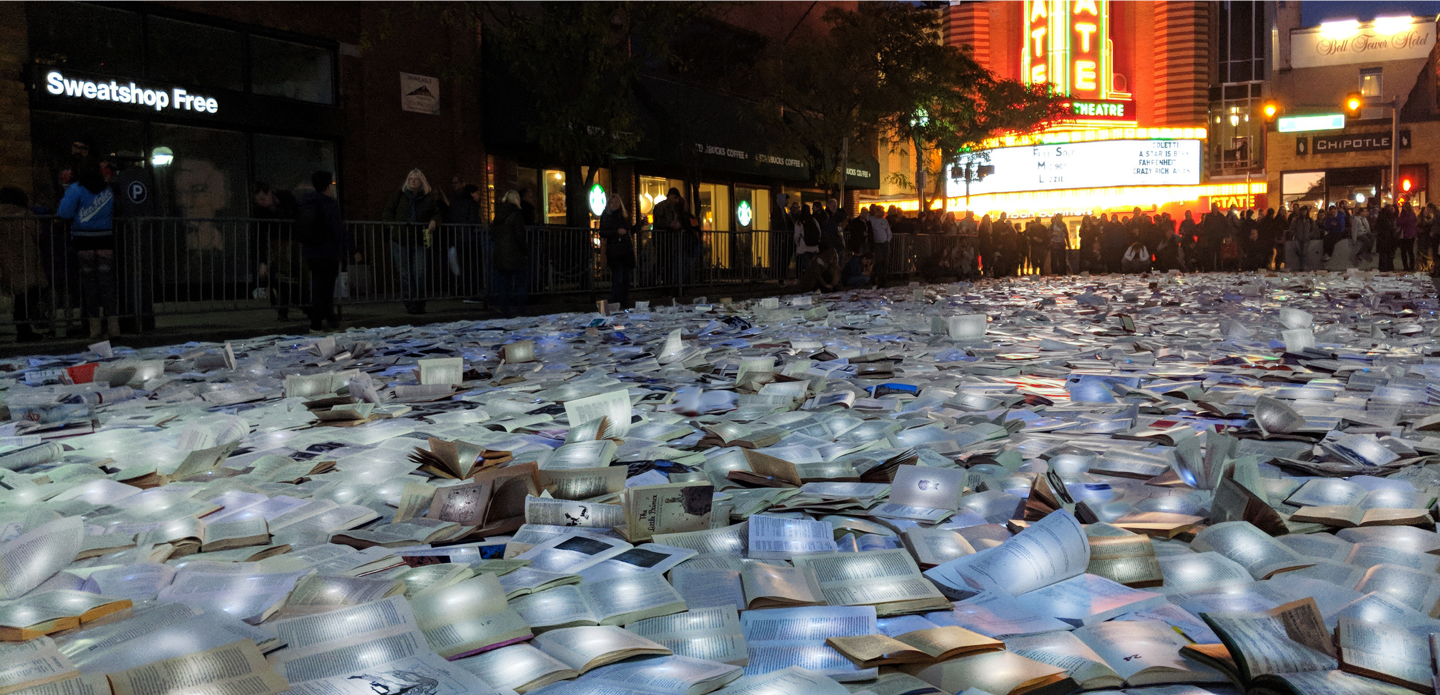 With the State Theatre in the background, a crowd of people look at illuminated books laid out on the street.