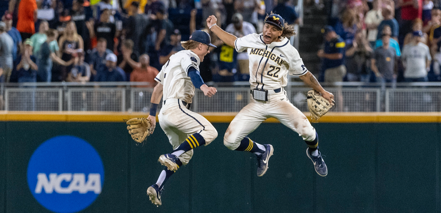 Two U-M baseball players celebrate on the field.