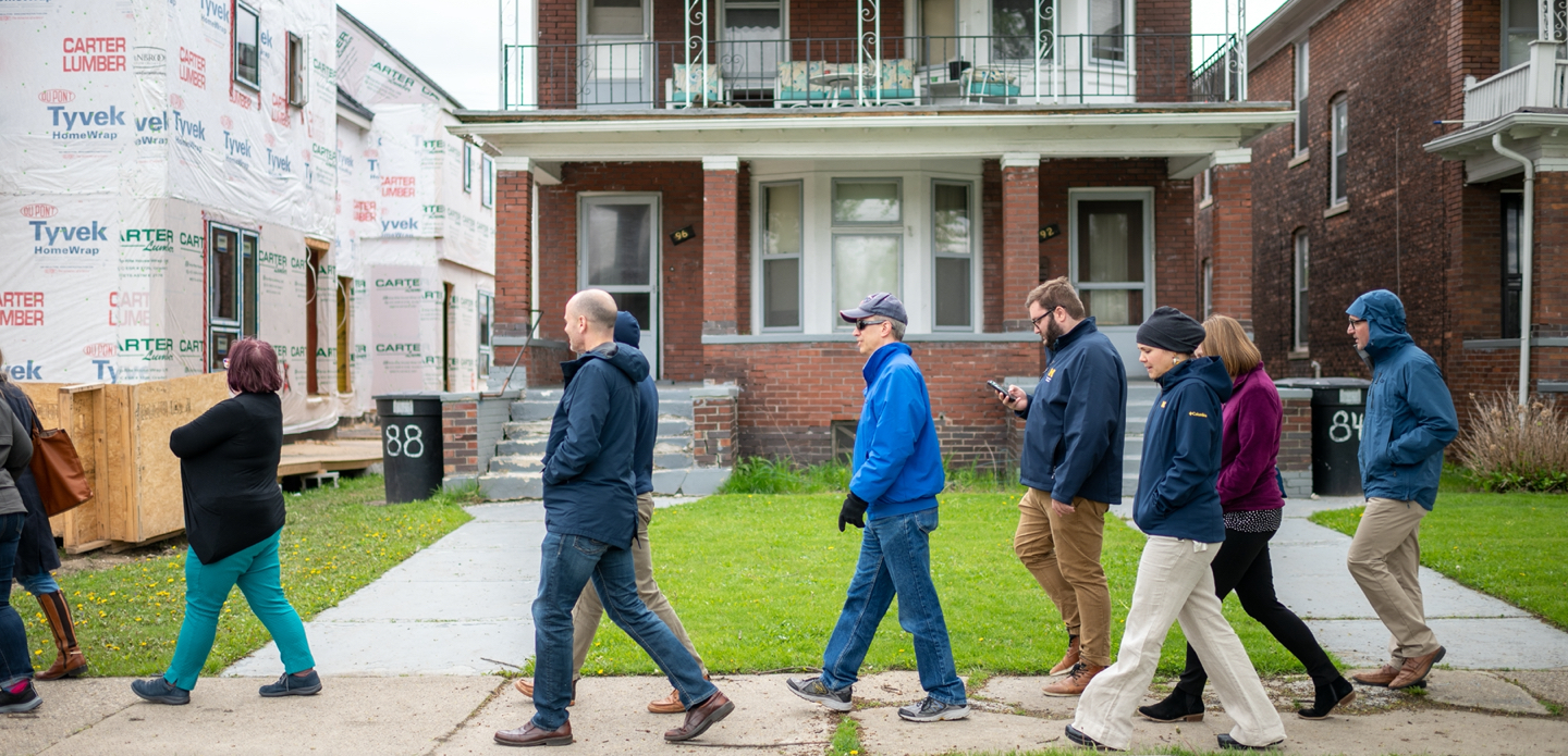 U-M faculty and staff walk past red-brick houses in Detroit.