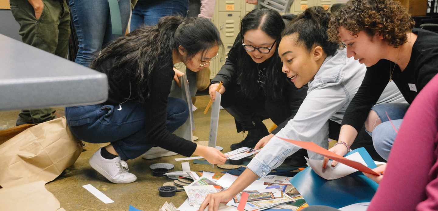 Four female U-M students look through printed materials.