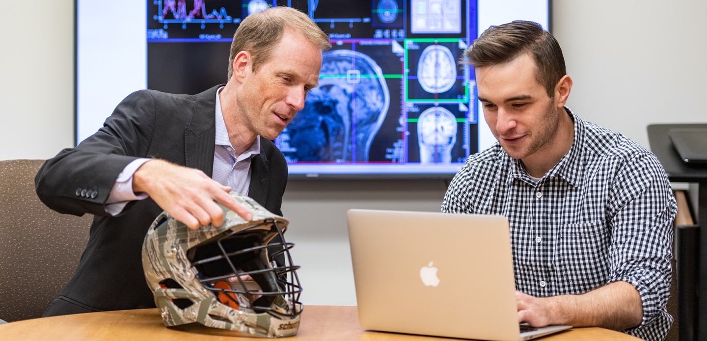 Two U-M researchers examine a football helmet, with a slide of concussion scans in the background.