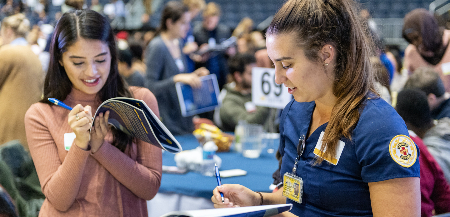 Two female U-M students take notes at the IPE event.