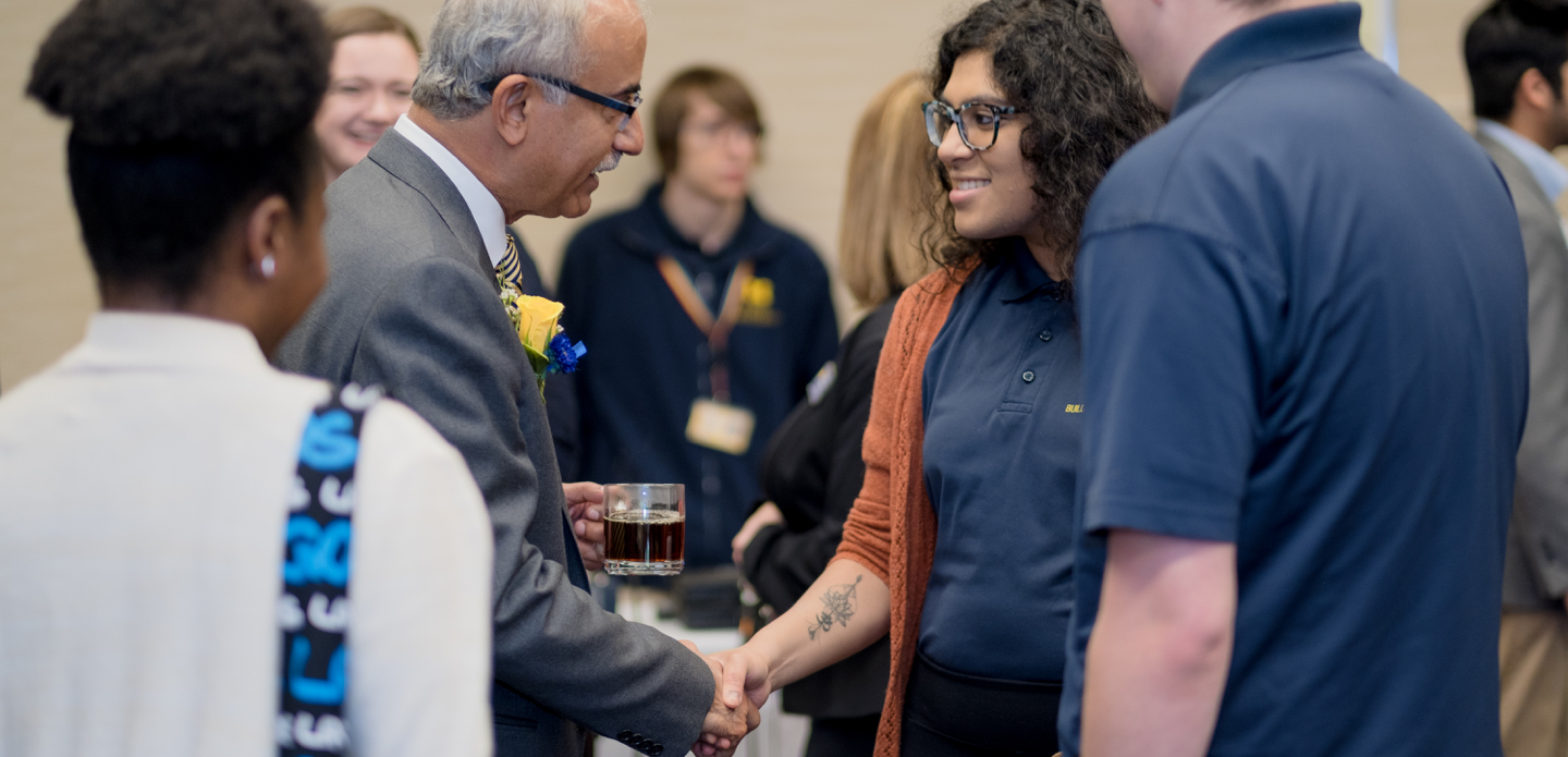New UM-Flint chancellor Debasish Dutta greets members of the campus community at an event.